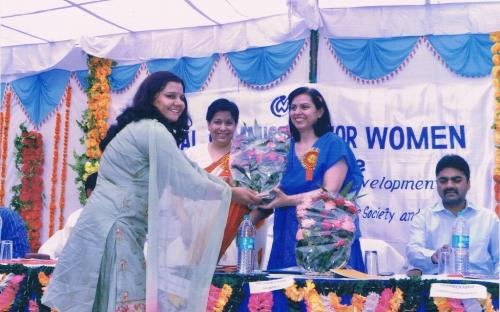 Ms. Naresh Yadav is presenting a bouque to Member, Charu WaliKhanna.Ex-Member, NCW Ms. Yasmin Abrar is standing on her right